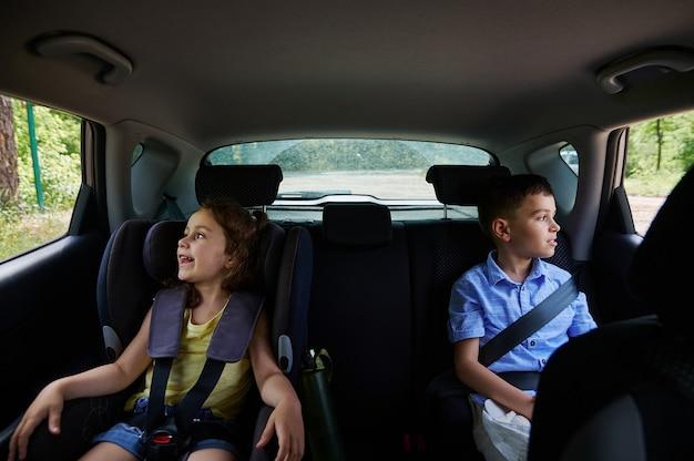 Angeschnallt zwei kinderpassagiere, junge und mädchen, die in einem sicherheitssitz im auto reisen. sicheres reisen mit kindern im auto