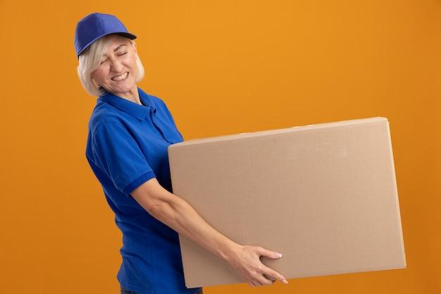 Angespannte blonde lieferfrau mittleren alters in blauer uniform und mütze