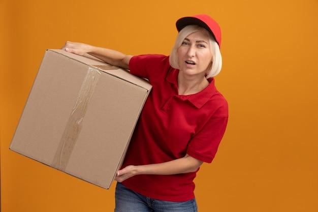 Angespannte blonde lieferfrau mittleren alters in roter uniform und mütze mit karton