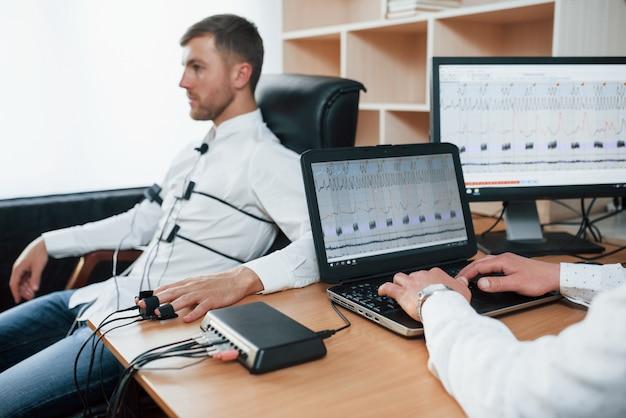 Angespannter blick. verdächtiger mann übergibt lügendetektor im büro. fragen stellen. polygraphentest