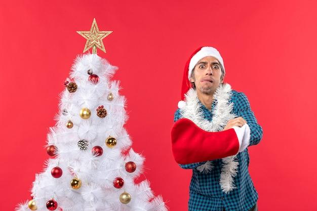 Angespannter junger mann mit weihnachtsmannhut in einem blau gestreiften hemd und etwas setzen