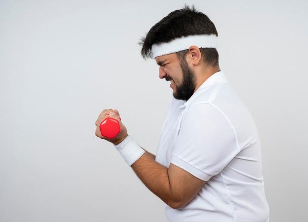 Angespannter junger sportlicher mann, der in der profilansicht das tragen des stirnbandes und des armbandes steht, die mit mit hanteln trainieren, die auf weißer wand mit kopienraum lokalisiert werden