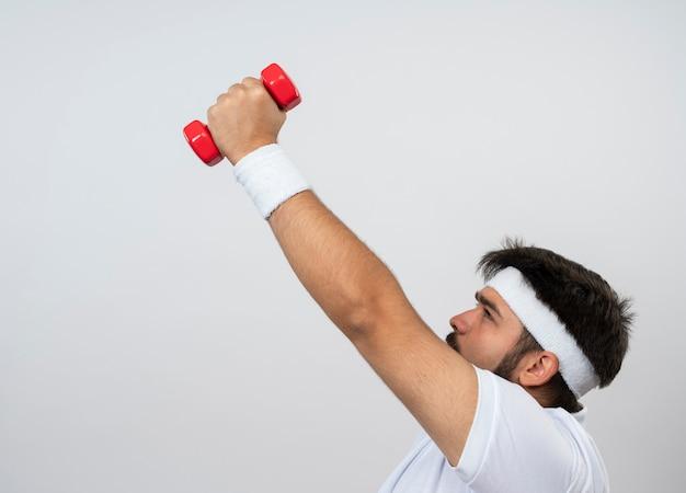 Angespannter junger sportlicher mann, der in der profilansicht steht und stirnband und armband trägt, die mit hanteln trainieren, die auf weiß mit kopienraum lokalisiert werden