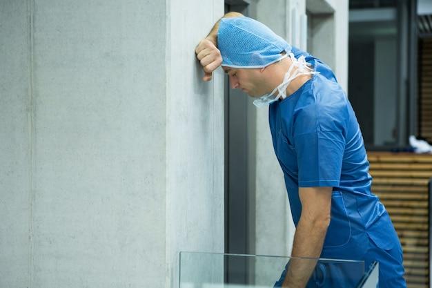 Angespannter männlicher chirurg, der an wand nahe aufzug lehnt