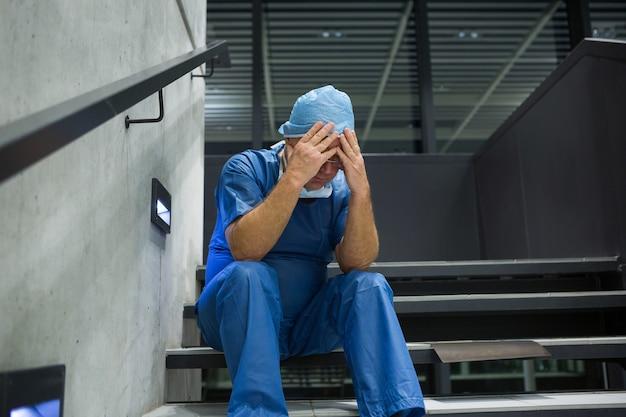 Angespannter männlicher chirurg, der mit den händen auf der stirn auf der treppe sitzt