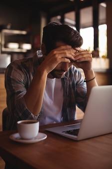 Angespannter mann, der mit laptop sitzt