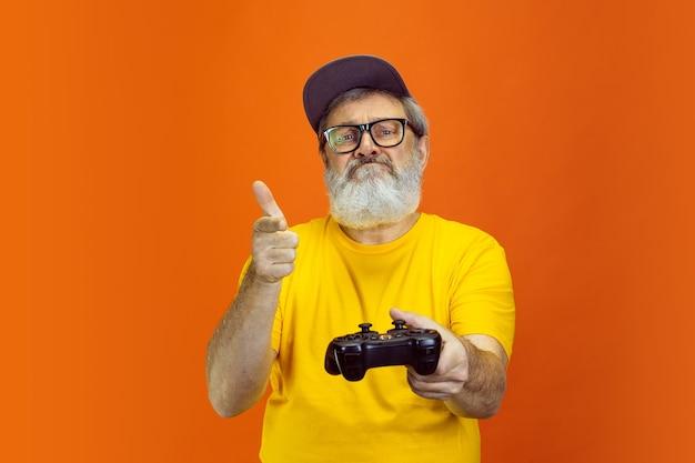 Angespannter spieler porträt eines älteren hipster-mannes, der geräte verwendet, die auf orange isoliert sind