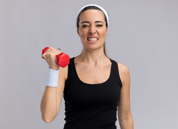 Angespanntes junges hübsches sportliches mädchen mit stirnband und armbändern, das hanteln isoliert auf weißer wand mit kopienraum anhebt