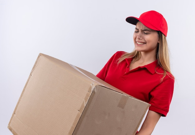 Angespanntes junges liefermädchen, das rote uniform und kappe hält, die schwere box lokalisiert auf weiß hält