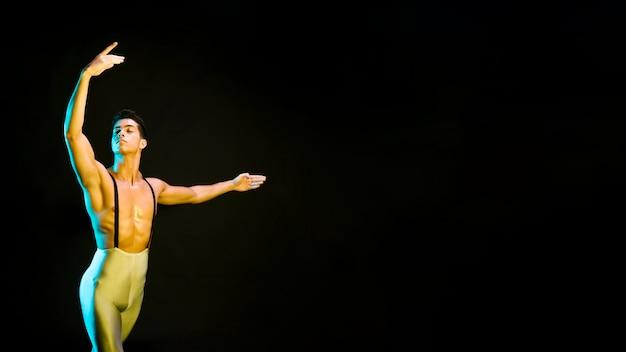 Angespornter männlicher balletttänzer, der im scheinwerferlicht durchführt