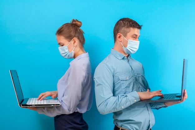 Angestellte, büroangestellte, mann und frau in medizinischen schutzmasken halten laptops in der hand