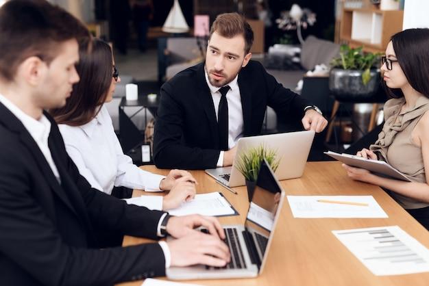 Angestellte der firma halten eine sitzung am tisch ab