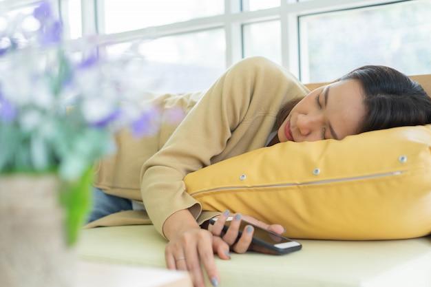 Angestellte frau, die an der couch schläft, nachdem sie sich am nachmittag eingeschlafen fühlt