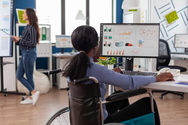 Angestellte mit behinderungen, behinderte pralysierte frau, die grafiken vom computer überprüft, der in einem finanzbüro arbeitet