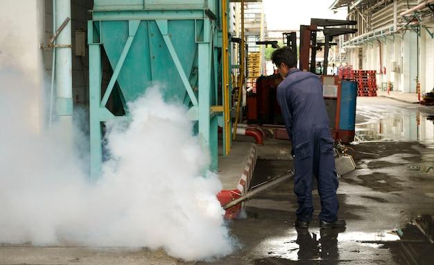 Angestellte töten moskitos, indem sie chemikalie im factore sprühen