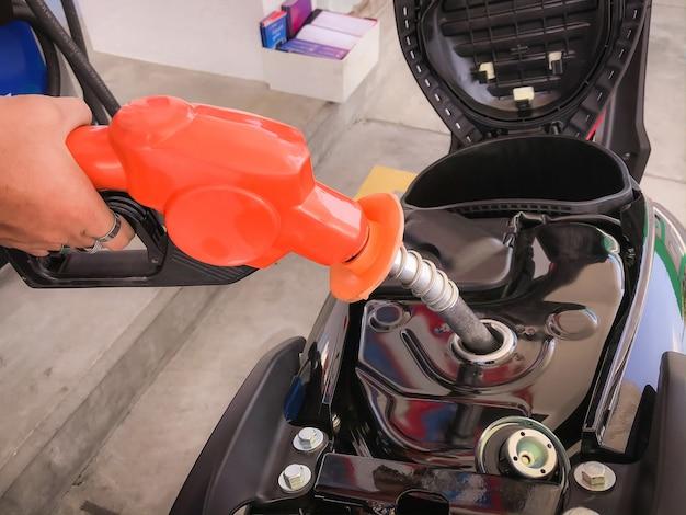 Angestellter, der den kraftstoffbehälter hält und benzylkraftstoff in den kraftstofftank des motorrads einfüllt.