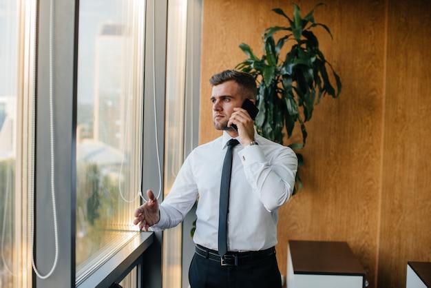 Angestellter im büro steht am fenster. finanzen