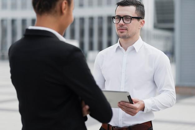 Angestellter mit den gläsern, die kollegen betrachten