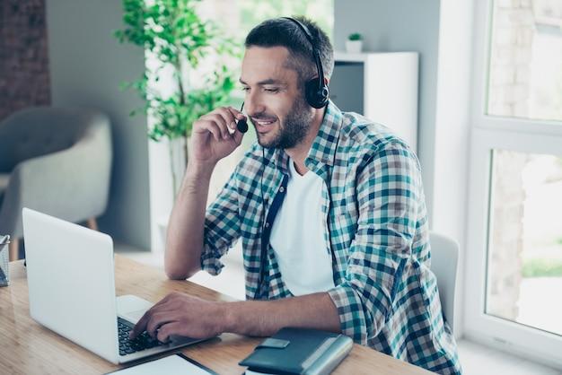 Angestellter mit einem blauen karierten hemd, das im büro arbeitet