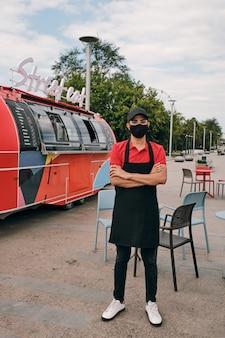 Angestellter von street food truck in uniform und schutzmaske