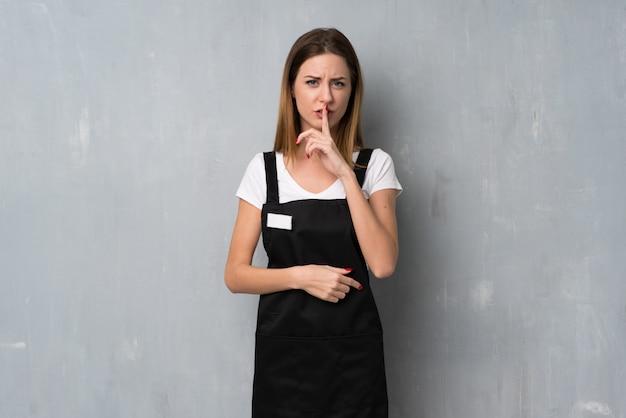 Angestelltfrau, die ein zeichen der ruhegeste finger in mund setzt zeigt