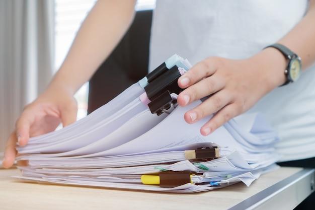 Angestelltfrauhände, die in den papierstapeldateien für das suchen unfertig überprüfen arbeiten