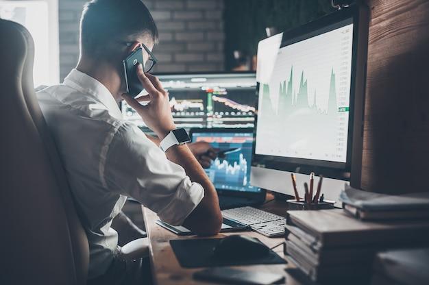 Angestrengter arbeitstag bei der arbeit. rückansicht eines jungen mannes in freizeitkleidung, der telefoniert und arbeitet, während er am schreibtisch im kreativbüro sitzt