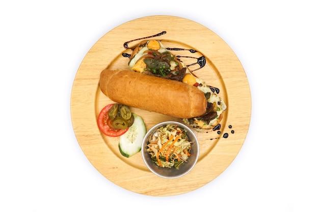 Angewandter korea- und amerika-hotdog-frühstücksstil mit breef-schweinekäse und gemüse auf der kreisholzplatte.