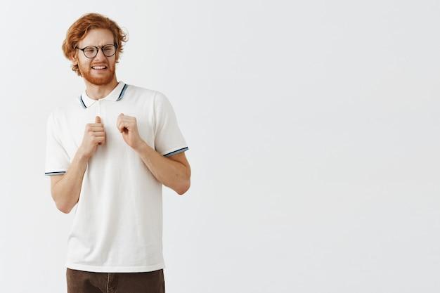 Angewiderter bärtiger rothaariger typ, der mit brille gegen die weiße wand posiert
