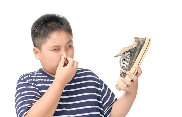 Angewiderter fetter junge, der ein paar stinkende schuhe hält