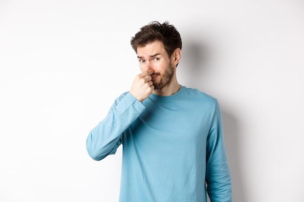 Angewiderter junger mann im sweatshirt schloss seine nase, schaute auf etwas mit schlechtem geruch und stand auf weißem hintergrund