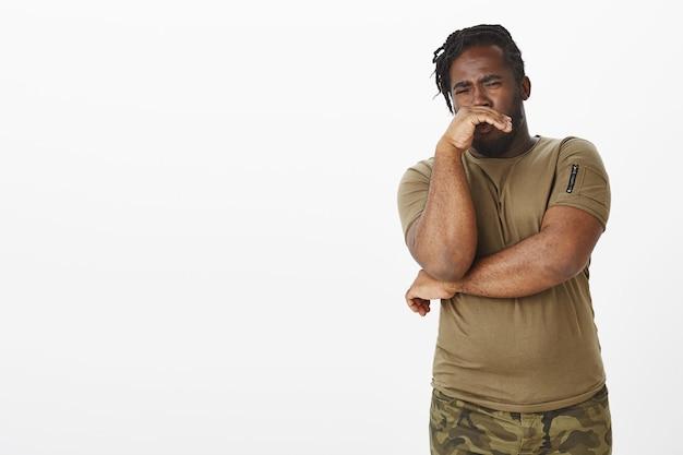 Angewiderter unglücklicher kerl in einem braunen t-shirt, das gegen die weiße wand aufwirft