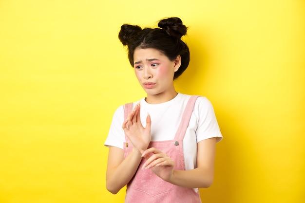 Angewidertes asiatisches mädchen, das die hände in die defensive hebt, etwas ekelhaftes blockiert, sich von abneigung und widerwillen abwendet und auf gelb steht.