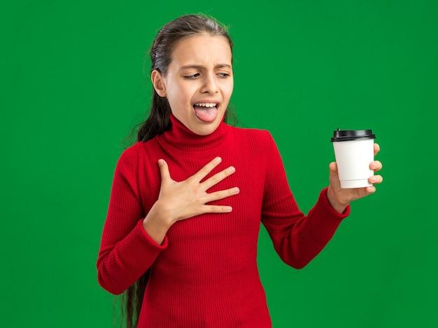 Angewidertes teenager-mädchen, das plastikkaffeetasse hält und betrachtet, die hand auf der brust hält und zunge zeigt, die auf grüner wand lokalisiert wird?