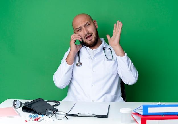 Angry junger männlicher arzt, der medizinische robe und stethoskop trägt, die am schreibtisch mit medizinischen werkzeugen sitzen, spricht am telefon und verbreitet hand lokalisiert auf grünem hintergrund