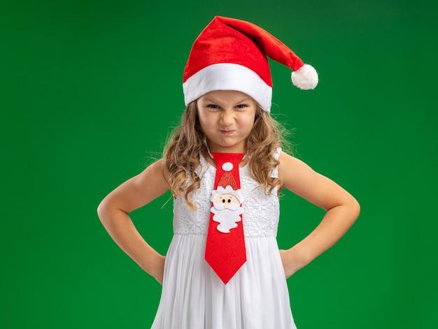 Angry kleines mädchen, das weihnachtsmütze mit krawatte trägt, die hände auf hüfte lokalisiert auf grünem hintergrund setzt