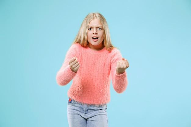Angry teen girl steht auf trendigen blauen studio hintergrund. weibliches porträt in halber länge. menschliche emotionen, gesichtsausdruckkonzept.