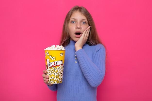 Angst, die hand auf die wange zu legen, schönes kleines mädchen, das einen blauen pullover trägt, der popcorn-eimer hält?