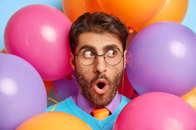 Angst kerl umgeben von partyballons posiert