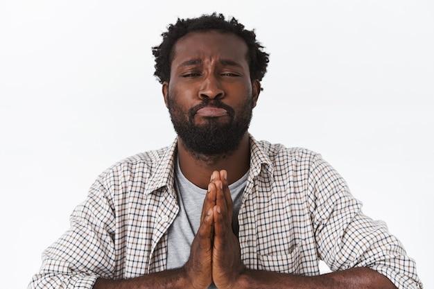 Anhänglicher gutaussehender afroamerikanischer bärtiger mann, der um vergebung oder gefallen bittet, die handflächen im gebet zusammendrücken, schmollend, albern schielen