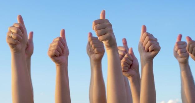 Anheben der hände mit daumen hoch auf klarem hintergrund des blauen himmels. menschen, die zustimmung und unterstützung ausdrücken