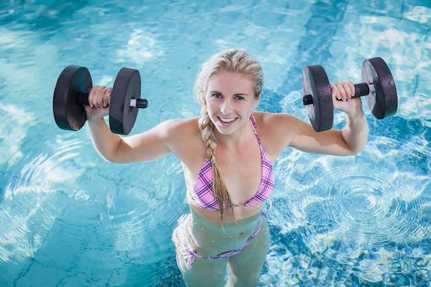 Anhebende dummköpfe der attraktiven frau im pool