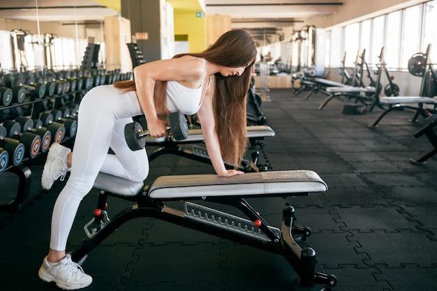 Anhebende gewichte der jungen eignungsfrau in der gymsportkleidung.