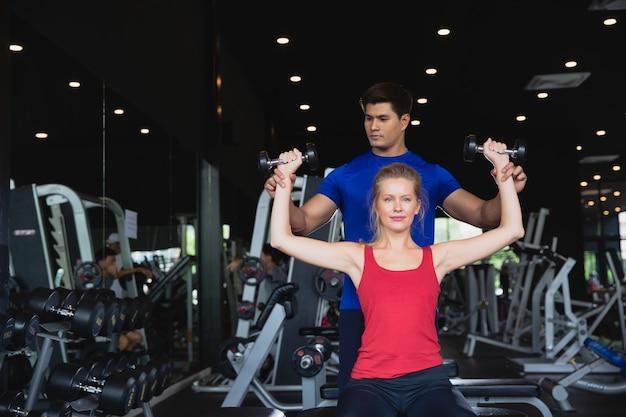 Anhebende gewichte des gesunden paartrainings, die an der turnhalle ausbilden