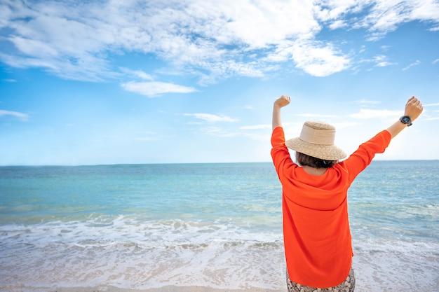 Anhebende hand der frau und schauen von ansicht von tropischem ozean mit blauem seehintergrund.