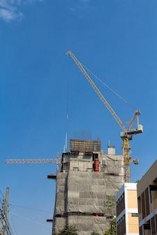 Anhebender Kran und Gebäude in der Baustelle