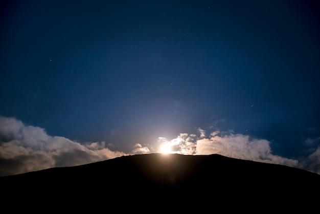 Anhebung des vollmondes über dem berg am dunkelblauen nachthimmel mit sternen