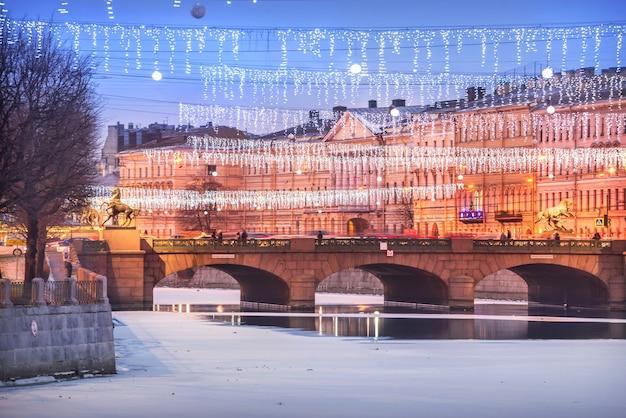 Anichkov-brücke über den fluss fontanka und neujahrsdekorationen am himmel von st. petersburg in einer winterblauen nacht