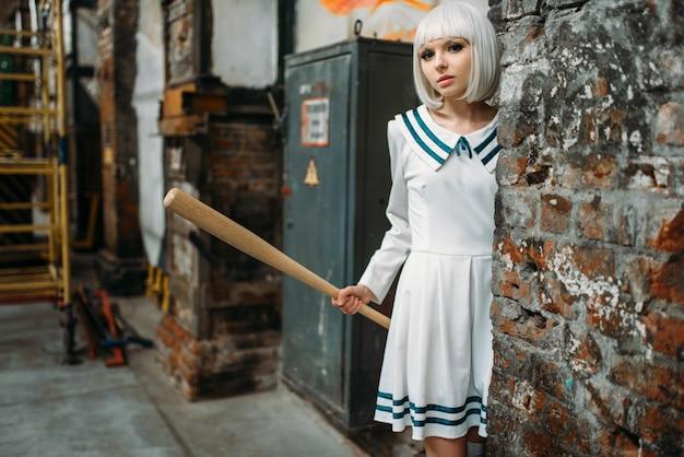 Anime mädchen mit baseballschläger. cosplay mode, asiatische kultur, puppe in uniform, süße frau mit make-up im verlassenen fabrikladen