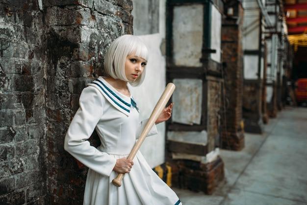 Anime-stil mädchen mit baseballschläger, lolita. cosplay mode, asiatische kultur, mangapuppe in uniform, süße frau mit make-up im verlassenen fabrikladen